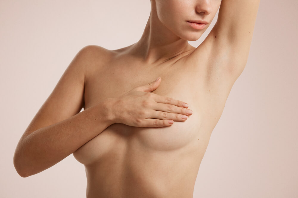 young woman with breast pain touching chest