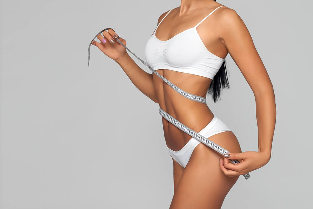 Attractive tan girl with measuring tape around the waist