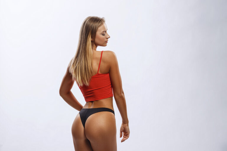Beautiful sexy fitness girl shows muscles